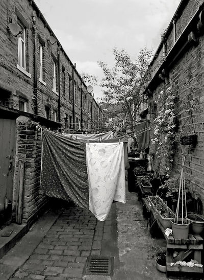 washing on lines in a back alley in terraced streets in hebden bridge Hebden Bridge Houses Yorkshire Alley Building Built Structure Clothesline England Hanging Outdoors Residential District Sky Street Terraced Houses Wall