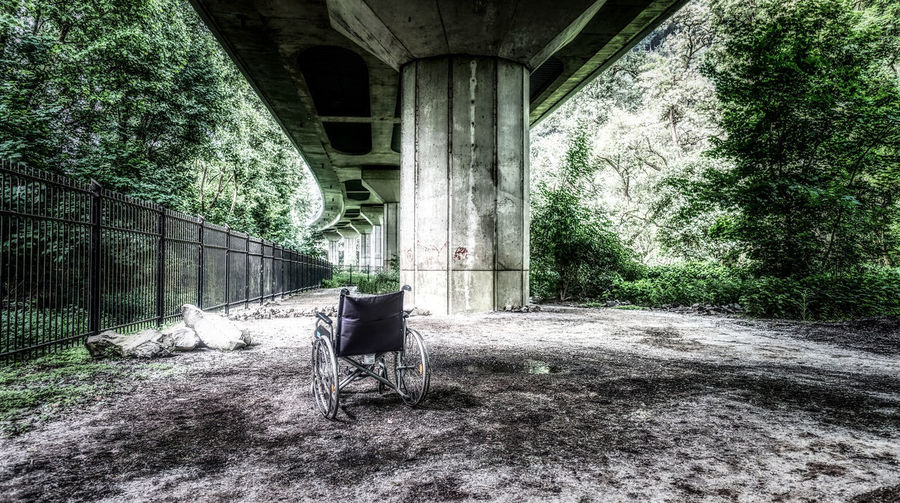 Rear view of man sitting on bridge