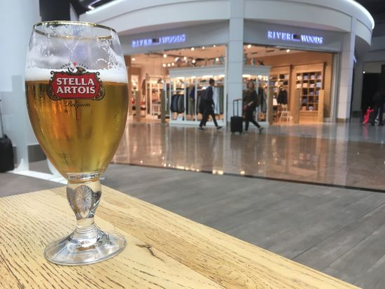 Brussels, Belgium - 15 August 2017: Stemmed glass of Stella Artois on a light wood table in a bar in the Brussels Airport (BRU) in Belgium. Brussels Brussels Airport Stella Artois Stella ❤ Brussels Belgium Stella Stellaartois