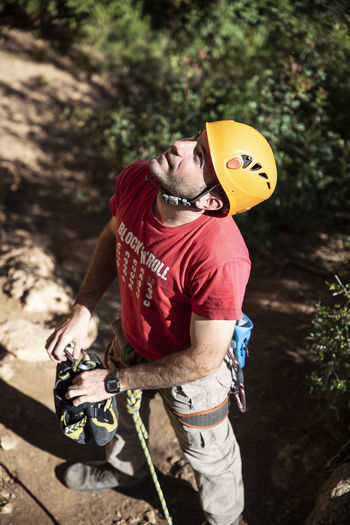 Looking there. One Person Helmet Real People Headwear Focus On Foreground Casual Clothing Holding Front View Young Men Outdoors Men Standing Day Protection Climber Vertical Worker Vertical Work Vertical Job Concentration Ready To Climb Red T-shirt Red