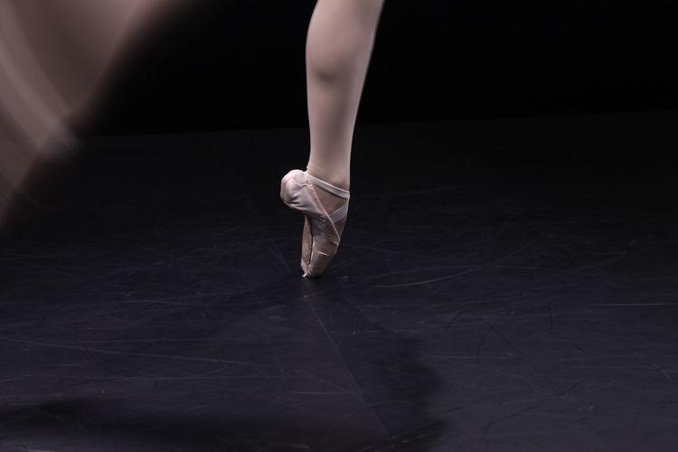 Low section of ballet dancer dancing against black background