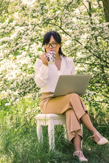 Woman holding laptop while sitting by plants
