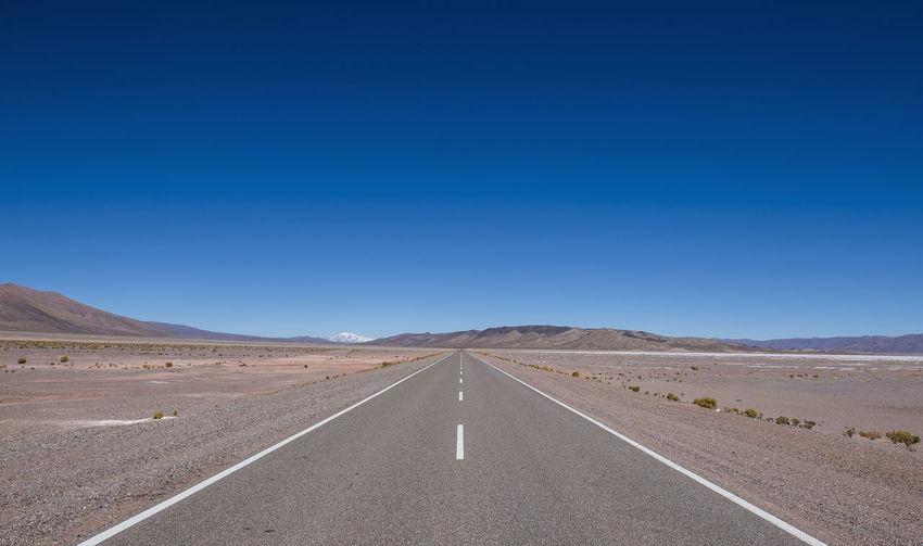 Road leading towards desert against clear blue sky