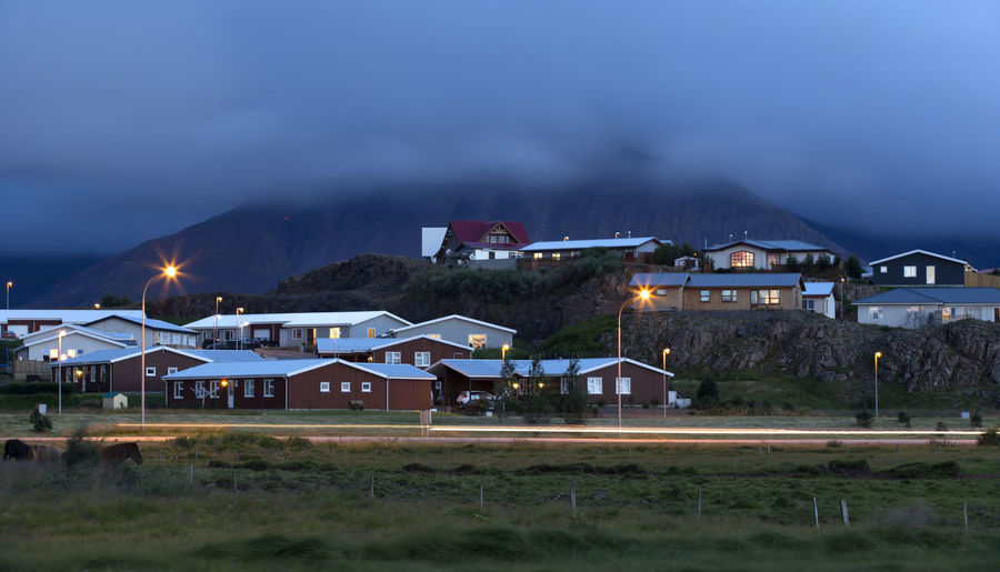 Tipical icelandic houses at the Foot of Mountains at night. Architecture Building Exterior Building; City; Cityscape Cottage; Countries; Europe; Exterior; House; North; Traditional; Exterior; Cottage; Culture; Building; Sea; Tranquil; City; Summer Iceland; Landscapes; Lifestyles Mountain; Nature; Night No People Nordic; North; Outdoors; Roof Scene; Summer Tranquil; Travel