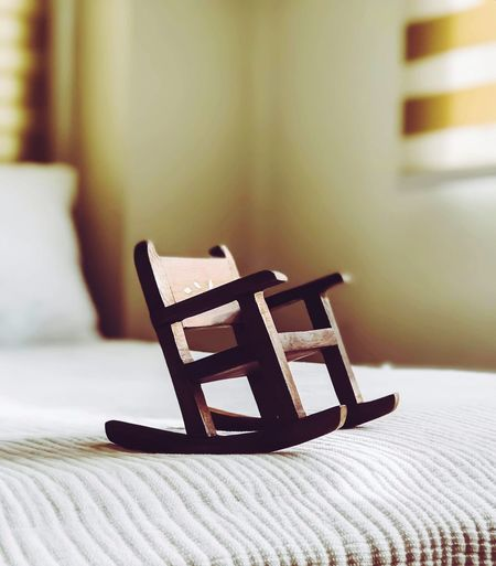 Close-up of small rocking chair on bed at home