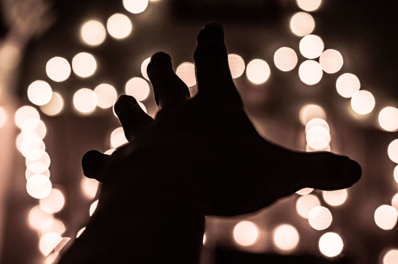 Silhouette hand of person against illuminated lights at night