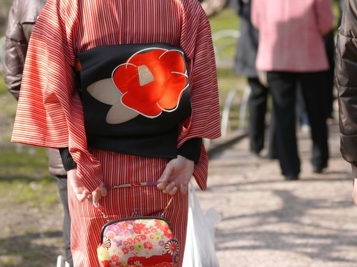 Midsection Of Woman Wearing Kimono Holding Purse On Footpath