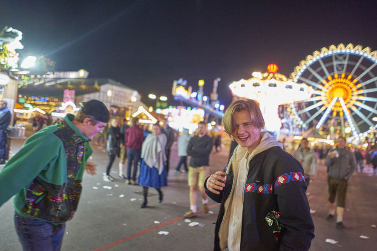 Drunk men standing at amusement park during night