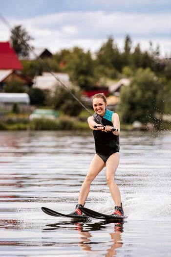 Full length of waterskiing in lake