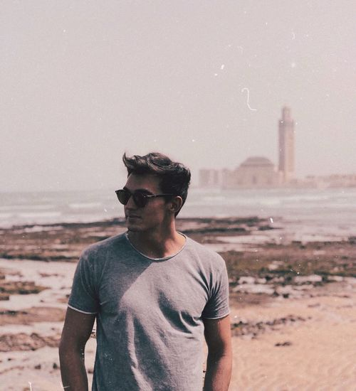 Young man wearing sunglasses standing on land against sea