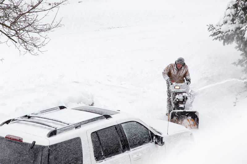 A man clearing heavy snow with a snowblower Bicycle Burried Car Clearing Cold Temperature Day Driveway Homeowner Leisure Activity Lifestyles Man One Person Outdoors People Real People Snow Snow ❄ Snowblower Snowblowing Storm Warm Clothing Winter