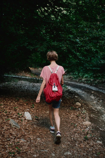 Full length rear view of teenage girl walking in forest