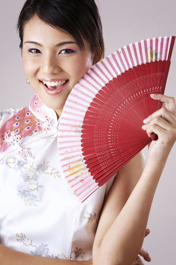 Portrait Of Smiling Young Woman Holding Hand Fan Against Gray Background