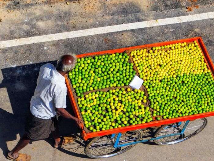 LEMONS SELLER ON ROAD High Angle View Day Seller In The Streets Juicy Citric Fruit Lemons One Person Full Length Real People Healthy Eating Food Fruit Men Food And Drink Casual Clothing Wellbeing Freshness City Outdoors Street Market Street Market Adult