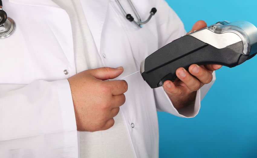 Midsection of doctor holding credit card reader