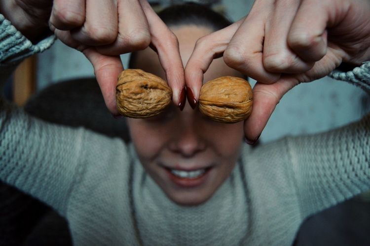 Close-up of woman covering face with walnut