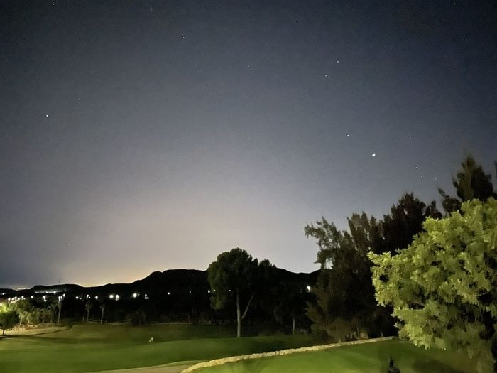 Scenic view of field against clear sky at night