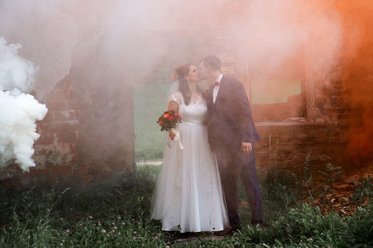 Full length of newlywed couple standing by abandoned built structure