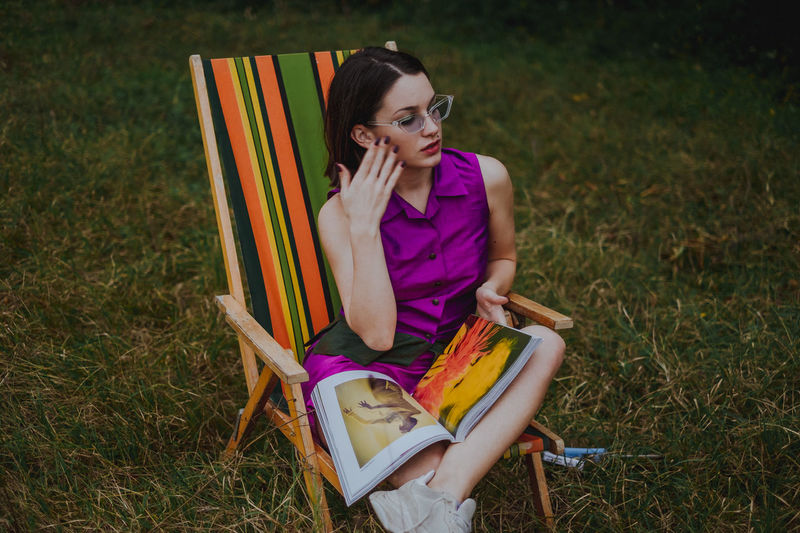 Woman With Magazine Sitting On Chair Over Field