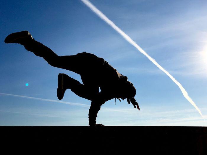 Man breakdancing against sky