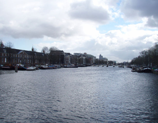 Amsterdam Architecture Blue Sky Boat Canal Clouds Distant Dramatic Sky Europe Mid Distance Netherlands Outdoors Reflect Reflection Ripples River Shadows Sky Texture Travel Trees Vanishing Point Water