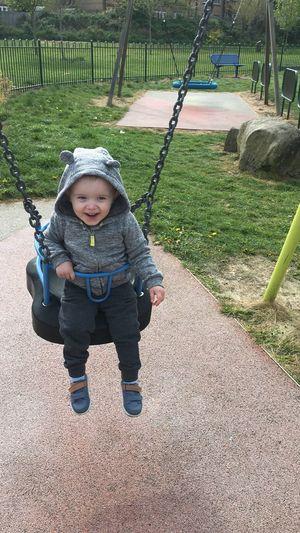 Full length of happy baby boy enjoying on swing at park
