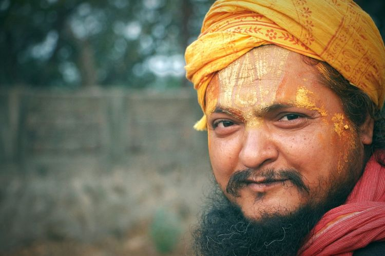 Portrait of smiling mid adult sadhu wearing headscarf