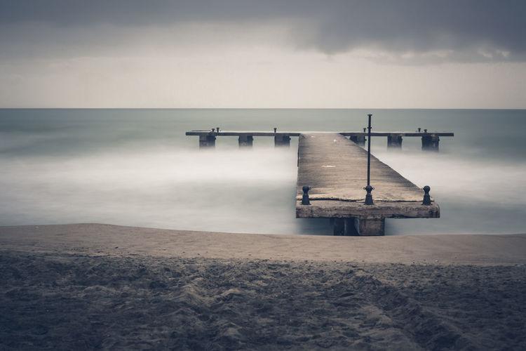 Sandy sea beach with old ruin wood pier in long exposure