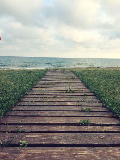 Boardwalk amidst sea against sky