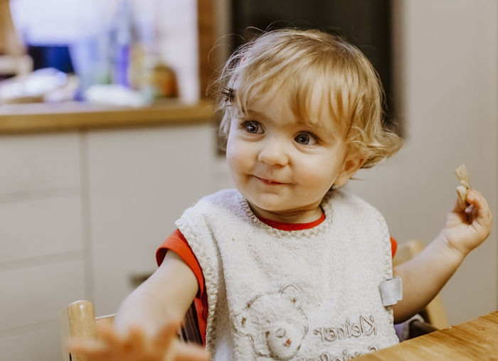 Baby girl sitting in highchair at table – Kempen, Germany Baby Eating Food And Drink Happy Hungry Sitting Babies Only Babygirl Babyhood Bib Child Childhood Close-up Cookie Germany Headshot Holding Indoors  Kitchen Portrait Smile Smiling Table Unhealthy Eating Waist Up