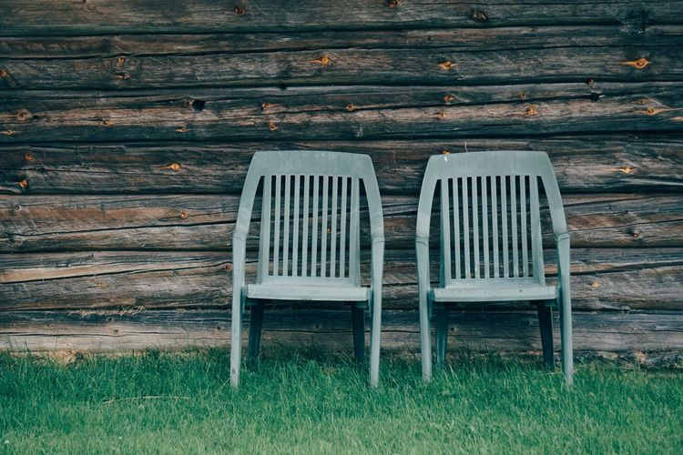 Empty chairs and table against wall in yard