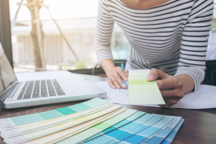 Midsection of businesswoman working with color swatch at office