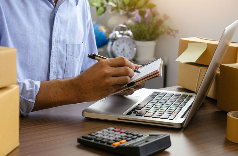 The man holding paper bills using calculator.
