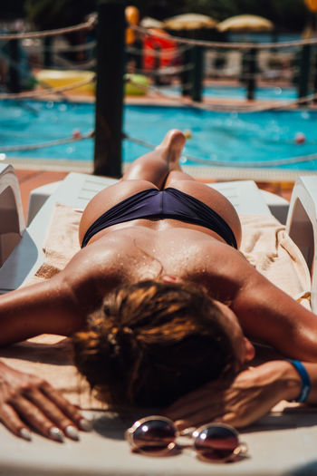 Adult Bikini Holiday Leisure Activity Lifestyles Lying Down One Person Outdoors Pool Poolside Real People Relaxation Resting Sun Sunbathing Swimming Pool Swimwear Trip Vacations Water Young Adult