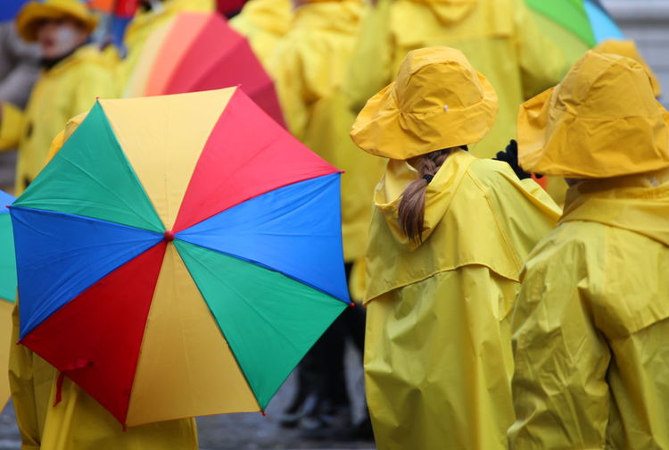 People in yellow raincoat standing on street during monsoon
