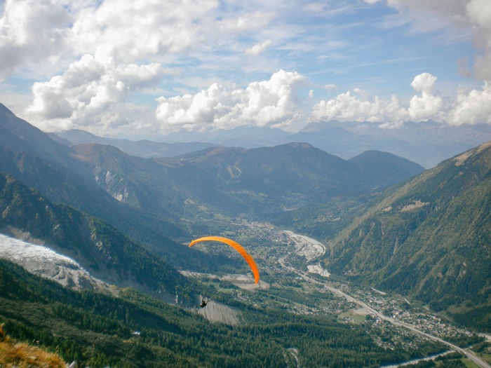 Scenic view of a person paragliding across mountains against sky