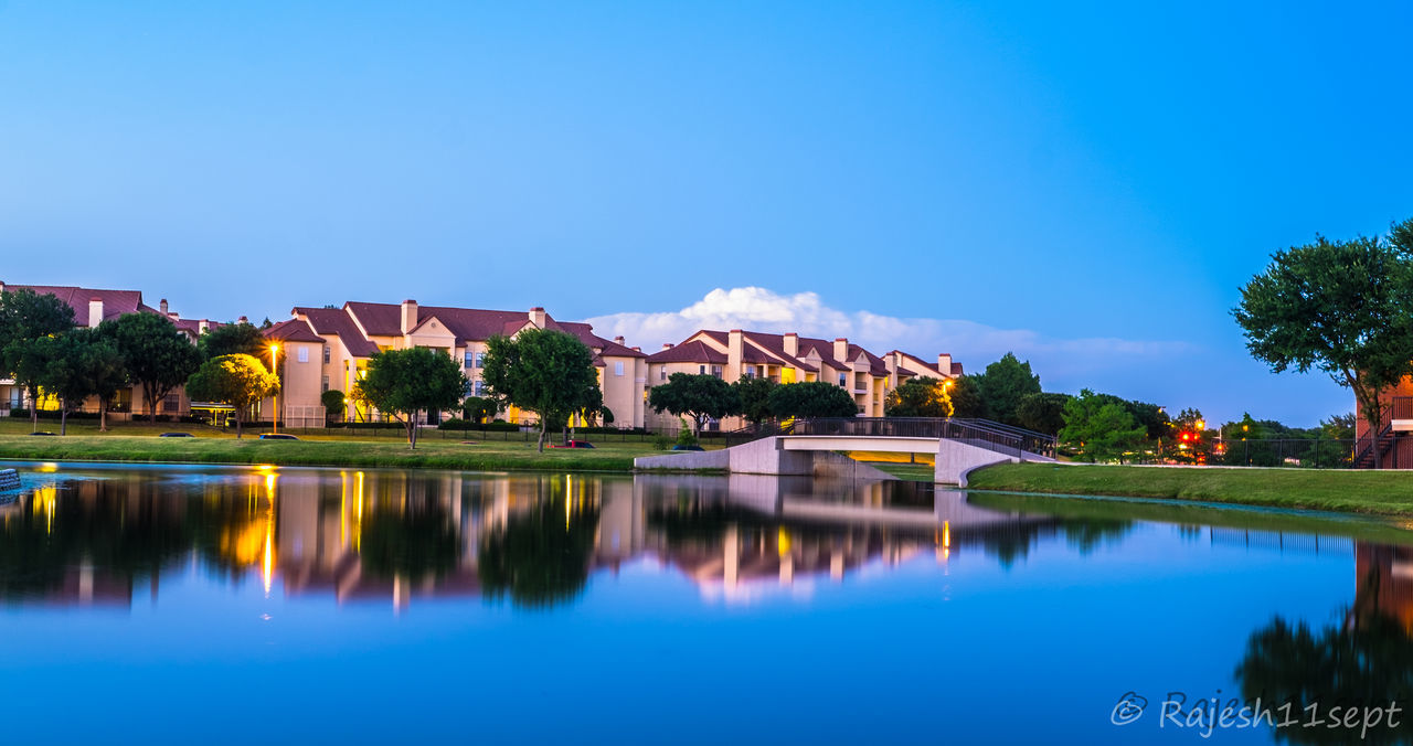 architecture, built structure, water, building exterior, reflection, blue, waterfront, house, tree, residential building, outdoors, no people, sky, nature, day, beauty in nature