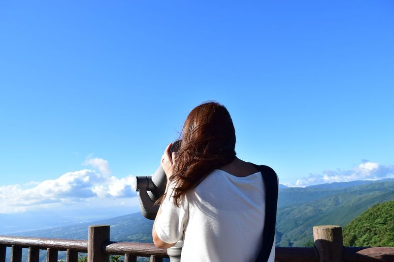 Rear View Of Woman Looking Through Binoculars Against Blue Sky