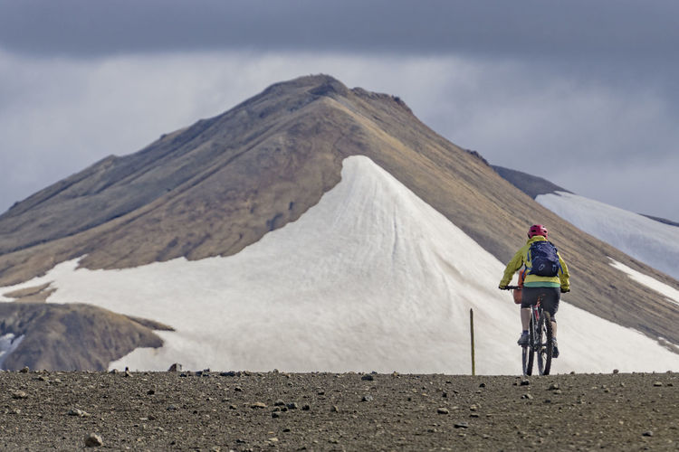 Rear view of person riding bicycle against snow covered mountain