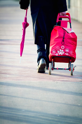 Adult Adults Only Day Farewell Human Body Part Long Goodbye Low Section Luggage One Man Only One Person One Woman Only Outdoors Pedestrian Pedestrian Walkway Pink Red Trolley Umbrella Walking Walking Away