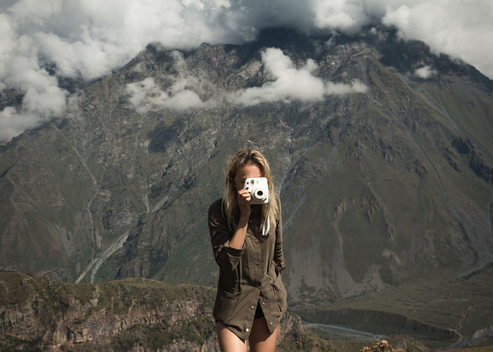 Portrait of young woman standing on mountain