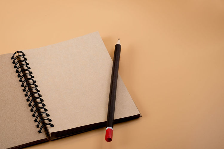 Close-up of open spiral notebook with pencil on brown background