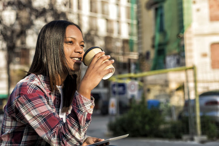 Young beautiful african american woman sitting outdoors in the city with a tablet pc while holding a take away coffee in a sunny day Food And Drink One Person Drink Young Adult Adult Holding Hair Food Long Hair Smiling Happiness Real People Technology Women Focus On Foreground Lifestyles Casual Clothing Hairstyle City Drinking Outdoors Take Away Relaxing Sitting Laugh Laughing Sunny Daylight