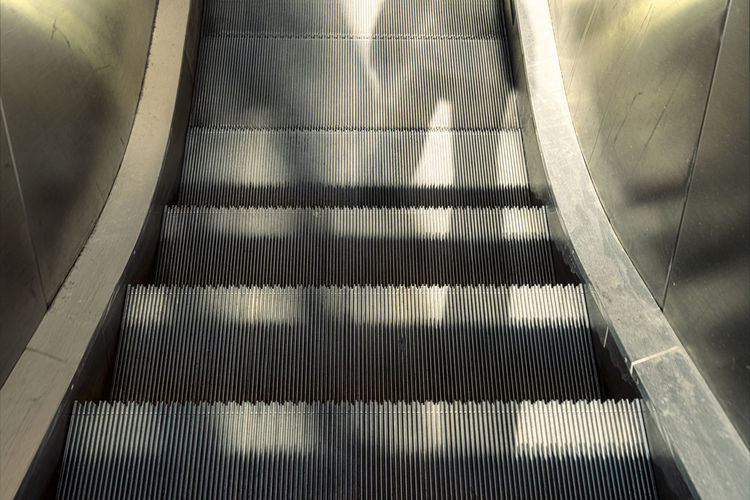 Escalator Shadow Standing person Anonymous Staircase Steps And Staircases Architecture Indoors  High Angle View The Way Forward Direction Railing No People Convenience Pattern Transportation Metal Modern Technology Sunlight Built Structure Day Moving Walkway