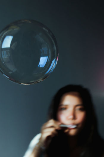 Young Woman Blowing Bubble At Home