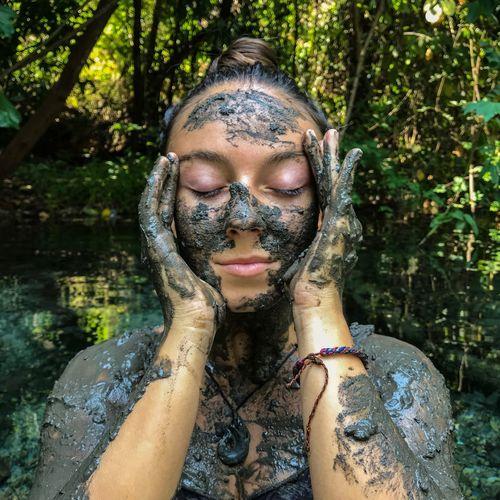 Woman Having Mud Bath In Forest