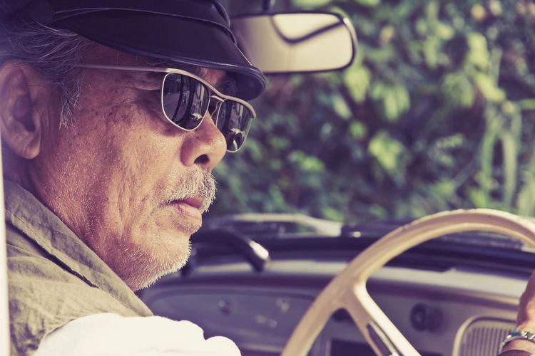 Close-up of senior man driving car