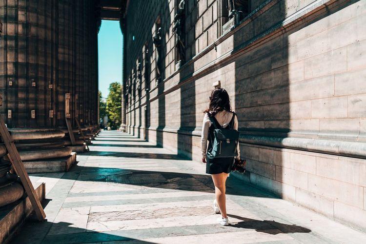 Woman walking on footpath by buildings