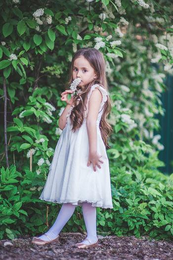 Girl standing against plants