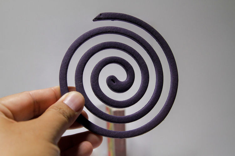 Cropped hand holding mosquito coil against wall
